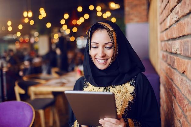 カフェに座っていると、タブレットを使用して伝統的な摩耗に身を包んだ豪華なイスラム教徒の女性。