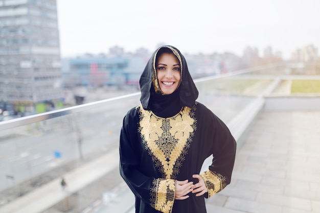 Gorgeous muslim woman in traditional wear looking at camera and posing while standing on rooftop.