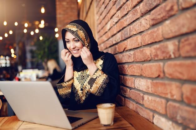 歯応えのある笑顔でゴージャスなイスラム教徒の女性は、カフェテリアに座っている間にオンラインショッピングのためにラップトップを使用して伝統的な服を着ています。机の上のコーヒー。