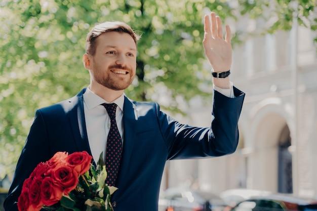 赤いバラの高価な花束とスタイリッシュなタキシードのゴージャスなきちんとしたひげを生やしたエレガントな男は、市内中心部の外の素敵なガールフレンドと晴れた日に幸せに会うために彼の手を振る