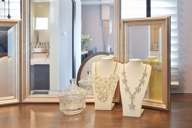 Gorgeous necklaces with mirors on the wooden table