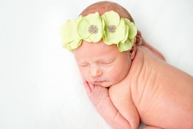 Великолепная новорожденная девочка в цветочном венке спит на белом одеяле