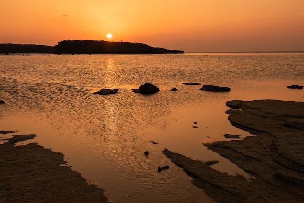 Gorgeous orange sunset going down behind the coastal rocks iriomote island