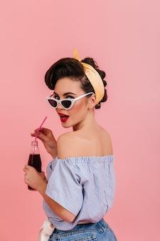 어깨 너머로보고 스트라이프 블라우스에 화려한 핀 업 소녀. 관능적 인 갈색 머리 아가씨 분홍색 배경에 고립의 스튜디오 샷.