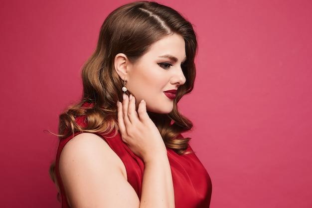 Шикарная пухленькая женщина с ярким макияжем в модном наряде на розовом фоне крупным планом портрет ...