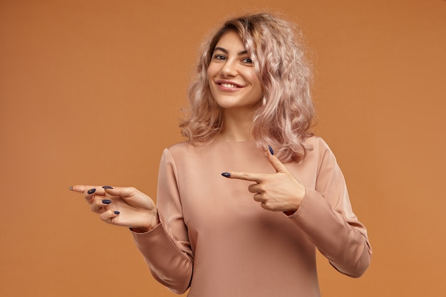 Splendida ragazza hipster dall'aspetto amichevole positivo con lunghe unghie nere e capelli rosati che sorride ampiamente alla telecamera e punta gli indici di lato