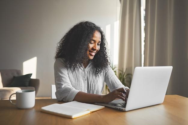 화려한 긍정적 인 젊은 어두운 피부의 여성 블로거가 일반 노트북에서 키보드를 사용하고, 웃고, 그녀의 여행 블로그를위한 새로운 콘텐츠를 만드는 동안 영감을 받고, 일기와 머그잔으로 책상에 앉아