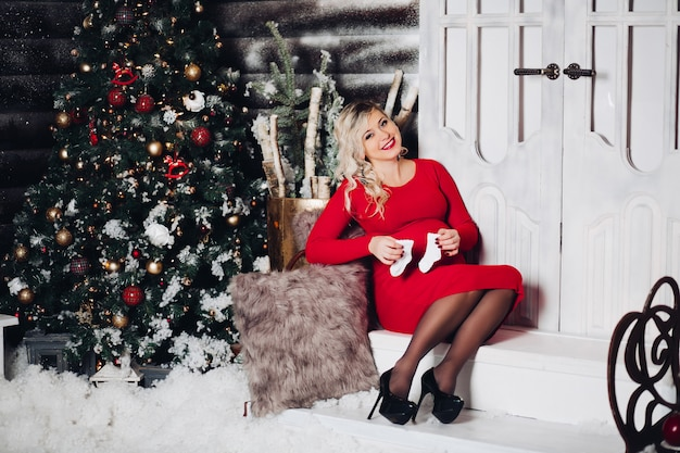 Gorgeous pregancy woman in red holding socks on stomach. christmas.