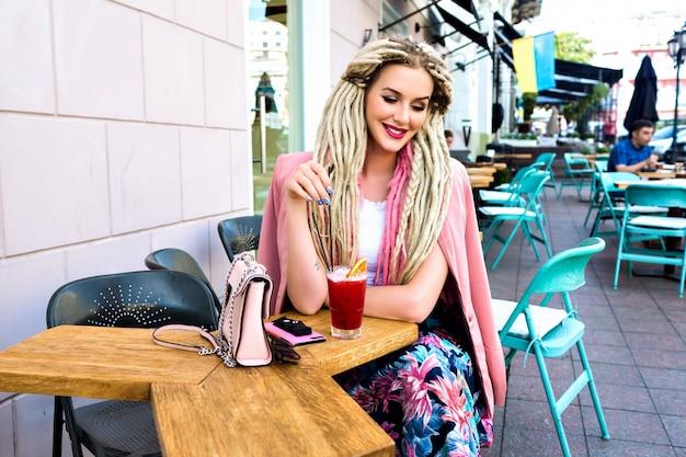 Великолепная довольно элегантная женщина позирует на террасе в городском кафе