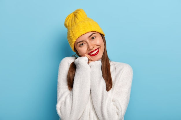 Gorgeous pretty feminine girl tilts head, wears soft white sweater, yellow headgear, has red lips, expresses positive emotions