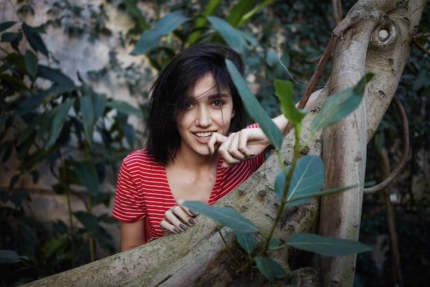 Splendida bella ragazza che fissa la telecamera con un sorriso giocoso, toccando misteriosamente le labbra mentre si cammina in giardino o parco, circondato da piante esotiche. natura, persone, stile di vita e concetto di tempo libero