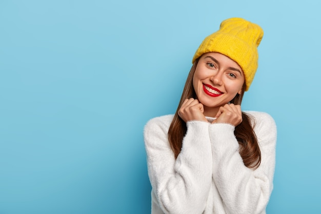 Gorgeous pretty young woman tilts head, has tender look, smiles happily, wears red lipstick, minimal makeup, dressed in yellow hat and white comfortable sweater, isolated over blue background