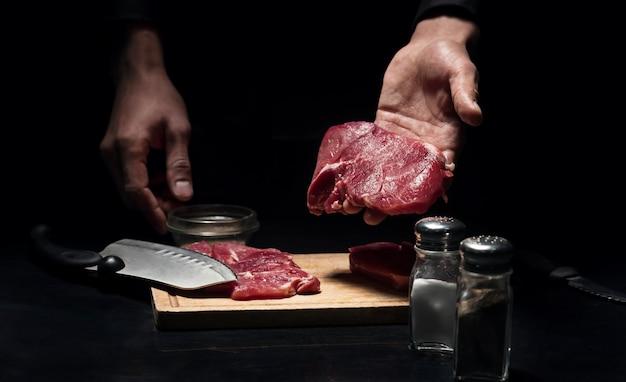 ゴージャスなレシート。レストランで調理中に肉を切り刻んだ後、肉を持っている男の手のクローズアップ。