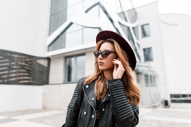세련 된 블랙 가죽 자 켓 포즈에 세련 된 모자에 빈티지 선글라스에 화려한 빨간 머리 hipster 젊은 여자