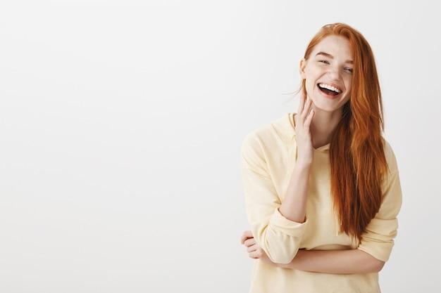 ゴージャスな赤毛の女の子は幸せから笑って、陽気に探して