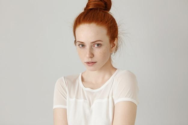 Великолепная рыжеволосая девушка с пучком волос и веснушками, одетая в белую блузку, слегка неуверенно пожимает плечами, смотрит с милой застенчивой улыбкой