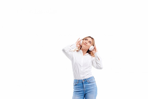 Великолепная рыжая дама слушает музыку по радио в наушниках и прыгает высоко. очаровательная девушка в повседневной одежде и наушниках танцует с развевающимися волосами на белом