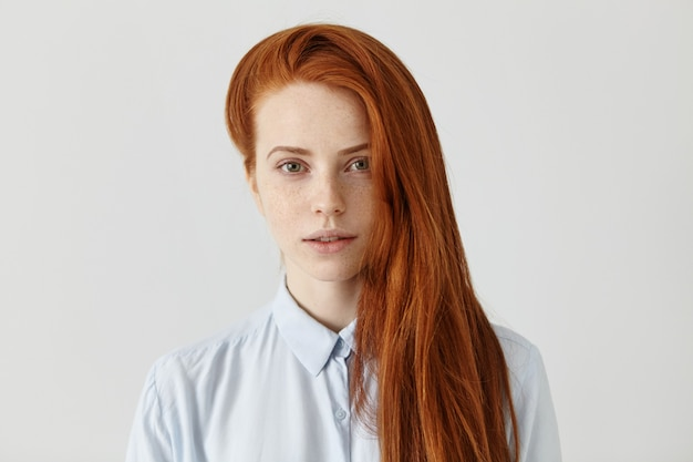 Великолепная рыжая студентка с длинной распущенной прической в голубой формальной рубашке
