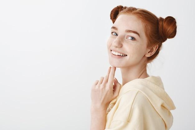 Splendida ragazza adolescente rossa girare, sorridendo felice