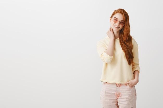 内気な笑顔のサングラスでゴージャスな赤毛の女性