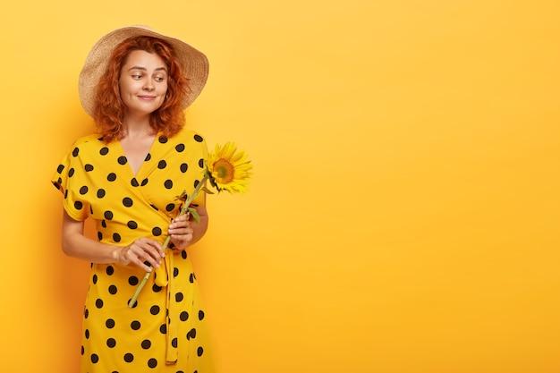 Splendida donna rossa in posa in abito giallo a pois e cappello di paglia