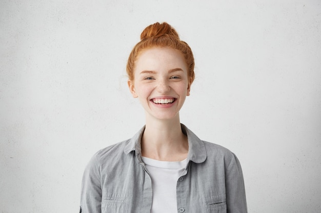 Великолепная довольная дама с завязанными рыжими волосами возбужденно смотрит в камеру