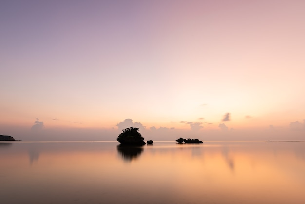 Gorgeous scene after sunset smooth sea surface islets in silhouette pastel tones sky