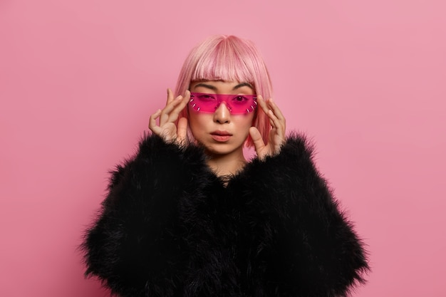 Gorgeous self confident serious woman wears trendy pink sunglasses, has rosy bob hair, dressed in fluffy warm black sweater, stands indoor, thinks about something. women, fashion, style concept