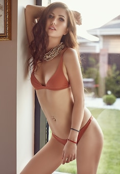 Gorgeous sensual model in fashion swimsuit posing near the window