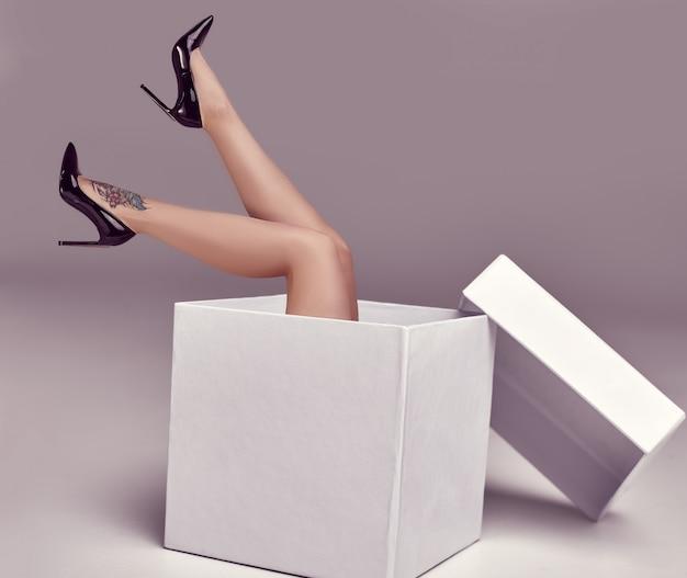 Gorgeous sensual woman posing in a big shopping box