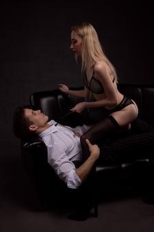 黒のソファで情熱的な抱擁で前戯の間にゴージャスなセクシーなカップル