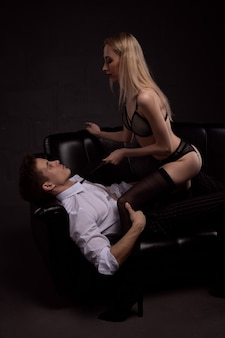 Gorgeous sexy couple during foreplay in a passionate embrace on a black sofa