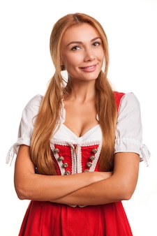 Gorgeous sexy red haired woman in traditional bavarian dress smiling to the camera with her arms crossed isolated on white. stunning oktoberfest waitress