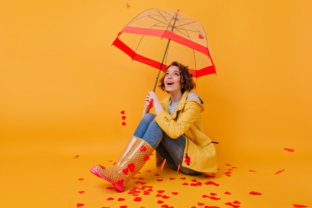 Gorgeous short-haired girl with beautiful eyes posing under parasol. indoor photo of romantic white female model sitting on yellow floor with umbrella.
