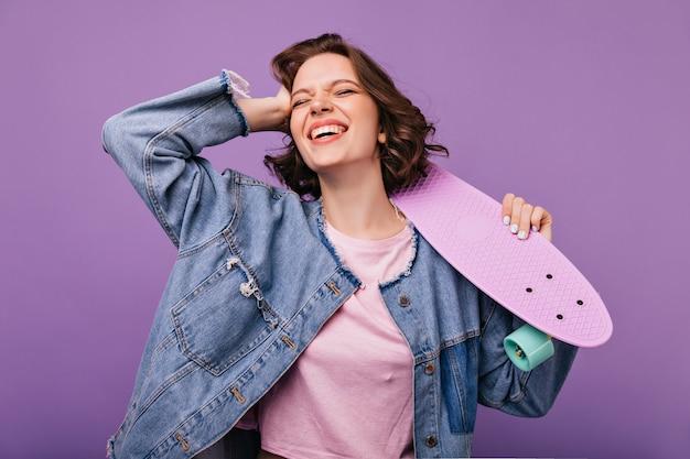 Splendida donna dai capelli corti in giacca di jeans che ride. incredibile signora caucasica con lo skateboard in piedi.