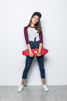 Signora splendida pattinatore che tiene skateboard rosso nelle sue mani isolato sul muro bianco