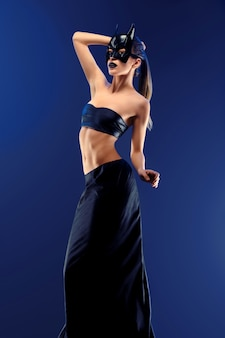 Gorgeous slim female fashion model wearing top and long black skirt