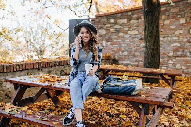 ゴージャスなスリムな女性は、秋の日に足を組んでテーブルに座っている短いジーンズを着ています