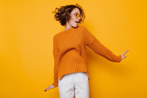 Великолепная стройная женщина в белых штанах прыгает на желтом фоне и смотрит в сторону