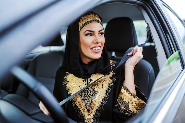 Великолепная улыбающаяся привлекательная мусульманская женщина в традиционной одежде сидит в своей дорогой машине и пристегивает ремень безопасности.