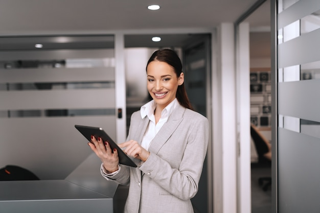 Gorgeous smiling brunette in formal wear using tablet. corporate firm interior. don't be busy, be productive.