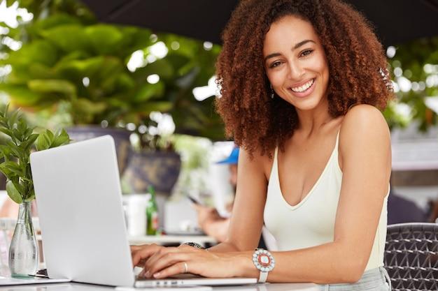 Великолепная улыбающаяся женщина наслаждается отдыхом в кафе, ведет видеозвонок через портативный ноутбук, пользуется приложением.