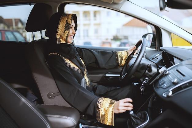 彼女の車を運転する伝統的な摩耗に身を包んだ豪華な笑顔のイスラム教徒の女性。
