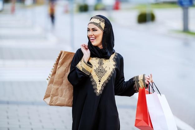 伝統的な服装でゴージャスな笑顔の肯定的なアラブの女性が通りを歩いて、彼女の買い物に満足していると感じて買い物袋を手に持っています。