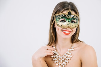Gorgeous smiling woman in masquerade carnival mask and necklace on white background