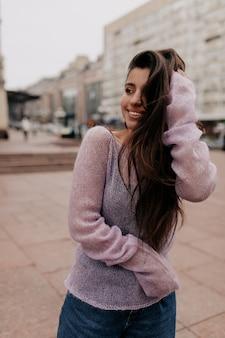 ぼやけた背景に街で喜んでポーズをとる長い髪のゴージャスな笑顔の女性。路上でふざけてポーズをとる黒い瞳の素敵な巻き毛の女性。