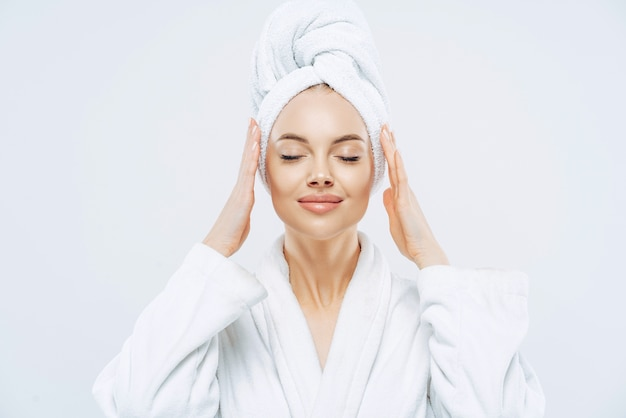 Gorgeous spa woman stands with closed eyes, keeps hands on towel wrapped on head, dressed in white bath robe, has healthy skin, natural makeup, well groomed complexion, poses indoor. beauty treatment