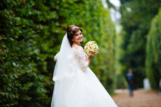 Gorgeous stylish blonde bride in vintage white dress walking in the park