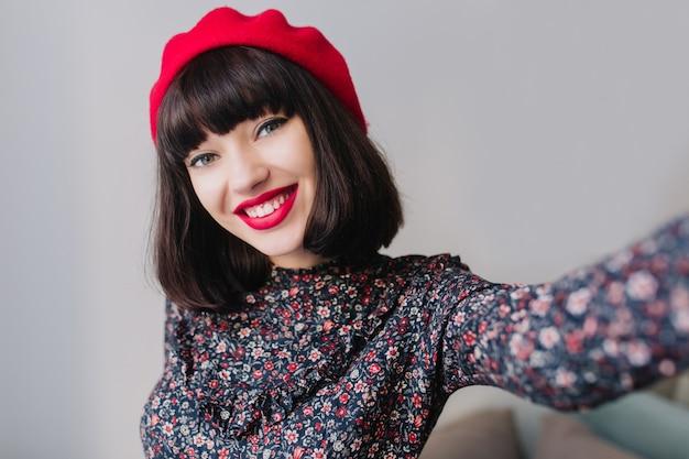셀카를 만드는 동안 널리 미소 꽃 무늬와 복고풍 드레스를 입고 화려한 세련 된 갈색 머리 소녀. 행복 한 얼굴 표정으로 유행 빨간 베레모에 사랑스러운 젊은 프랑스 여자의 클로즈 업 초상화
