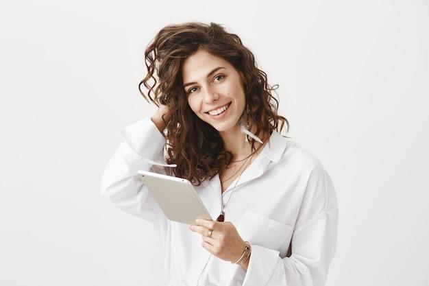 Splendida donna alla moda utilizzando la tavoletta digitale